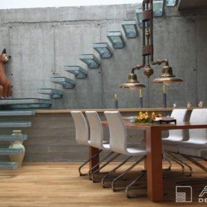 Bytový architekt doplnil prostor jídelny, kde dominantním prvkem je neomítnutý surový beton a skleněné schodiště, o elegantní dýhovaný stůl.